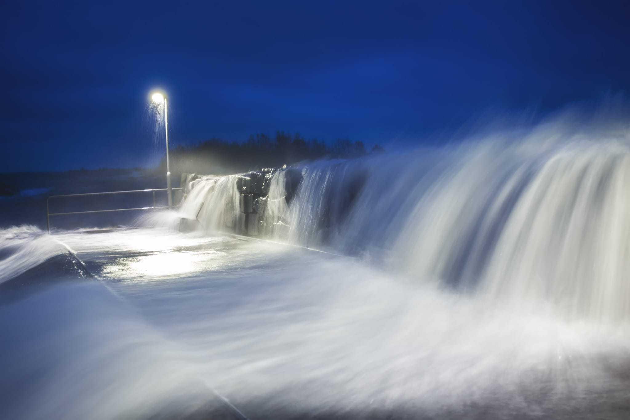 Vågbrytaren vid Väggahamnen översköljs av höga vågor - Ludwig Sörmlind